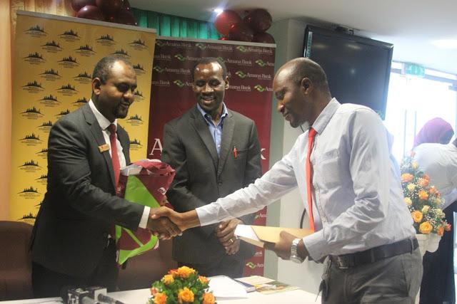 Stephano Matesi akipokea hati ya kiwanja kutoka kwa mkuu wa idara ya biashara wa benki ya amana Munir Rajab leo jijini Dar es salaam