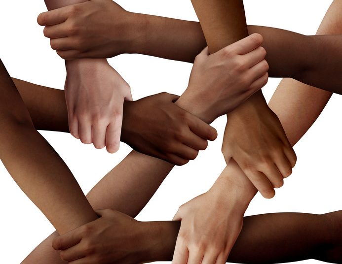 Diversity teamwork as a group of diverse people holding arms as a multiracial society and multicultural community joined  and united as a strong together and togetherness concept.