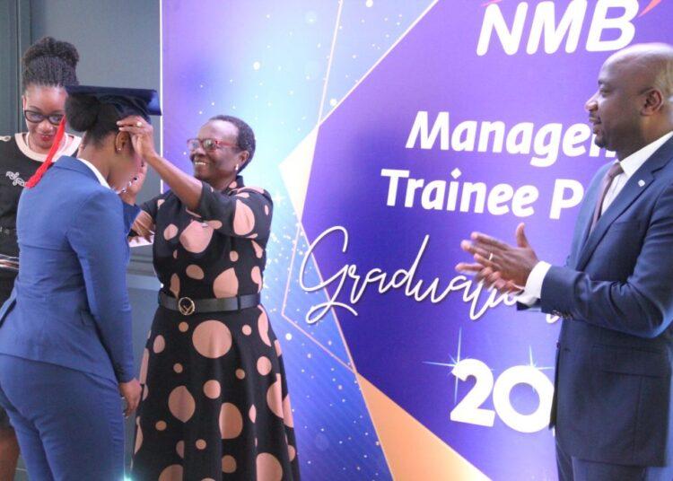 Mjumbe wa Bodi ya wakurugenzi ya Benki ya NMB, Margareth Ikongo akimvalisha kofia mmoja wa wahitimu katika Program ya mafunzo ya uongozi ya Mwaka 2018-20202 ya benki ya NMB
